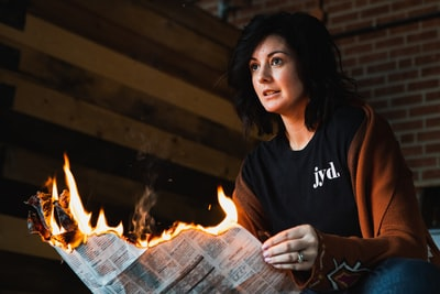 woman holding newspaper with flame kansas zoom background