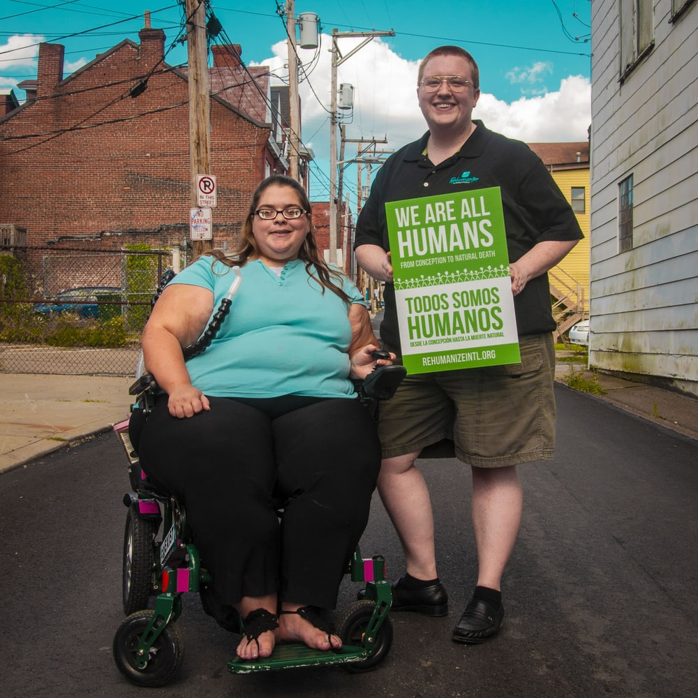 woman sitting on wheelchair beside man holding we are all humans sign