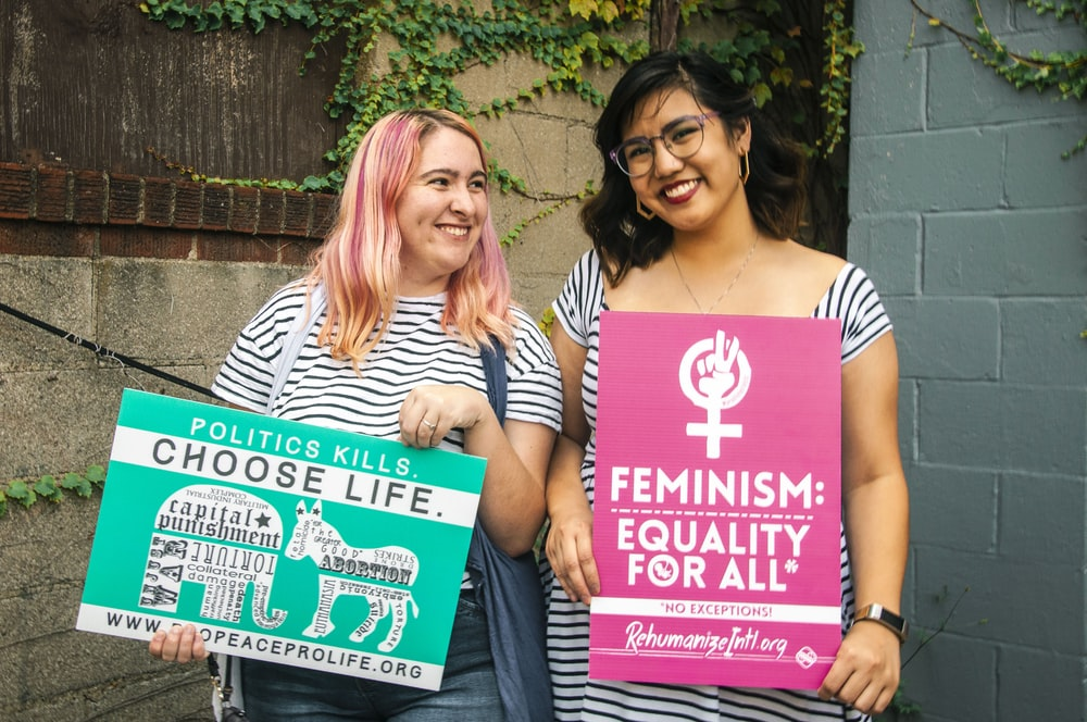 two smiling women standing while holding banners near concrete wall