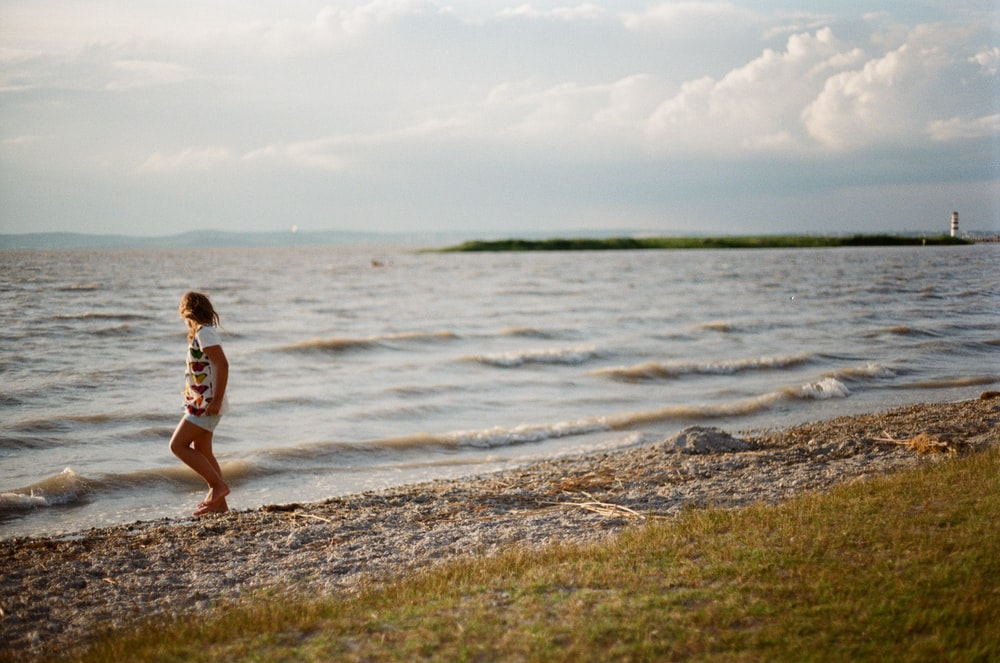 person walking on seashore during daytime