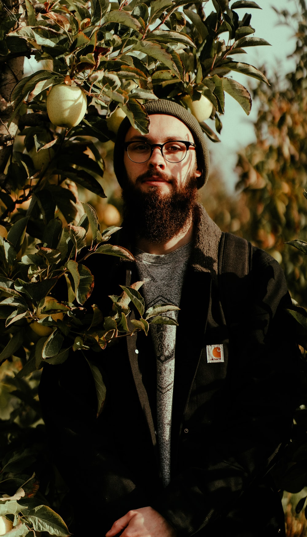 selective focus photography of man standing behind plants
