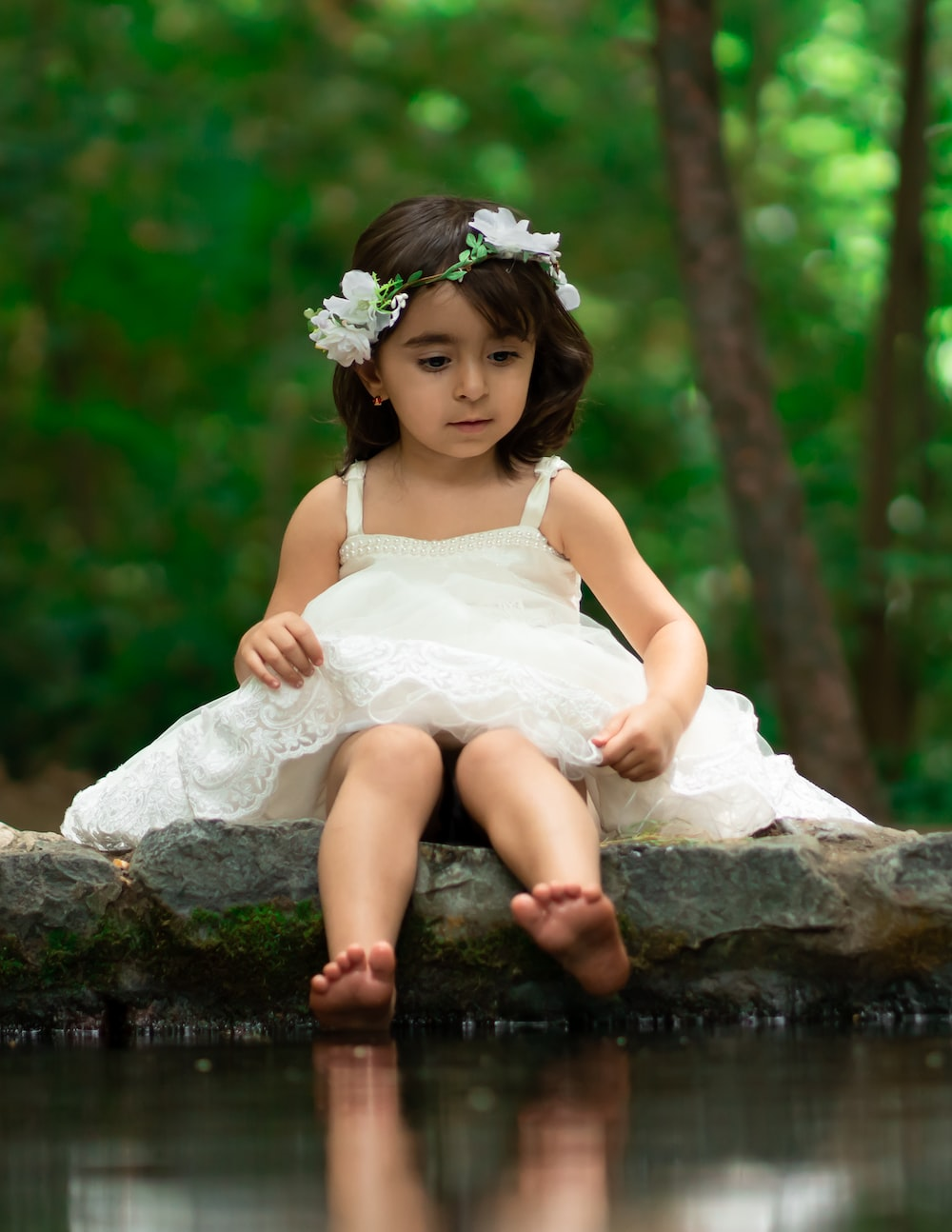 girl in white dress by body of water at daytime