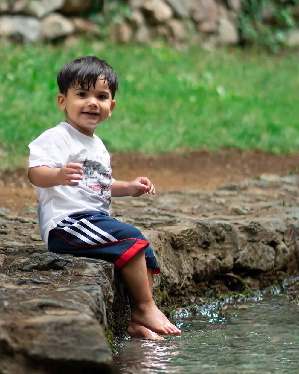 boy sitting by rock by body of water
