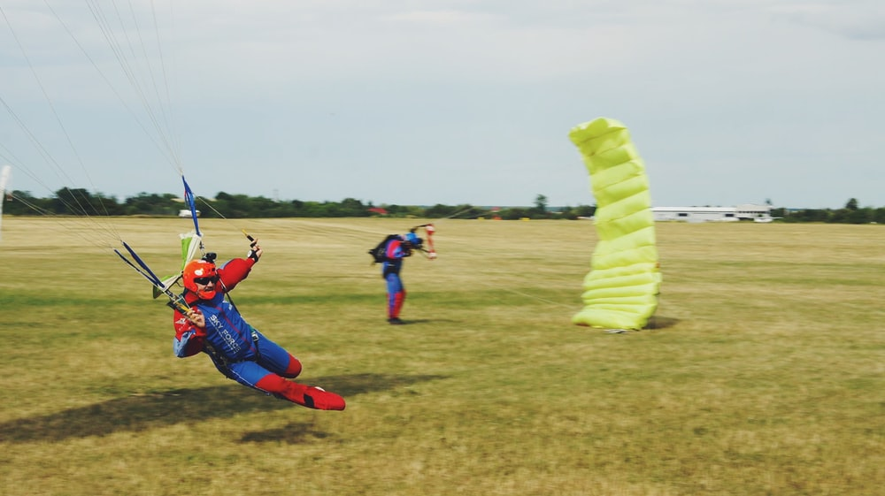 man standing on field with parachute