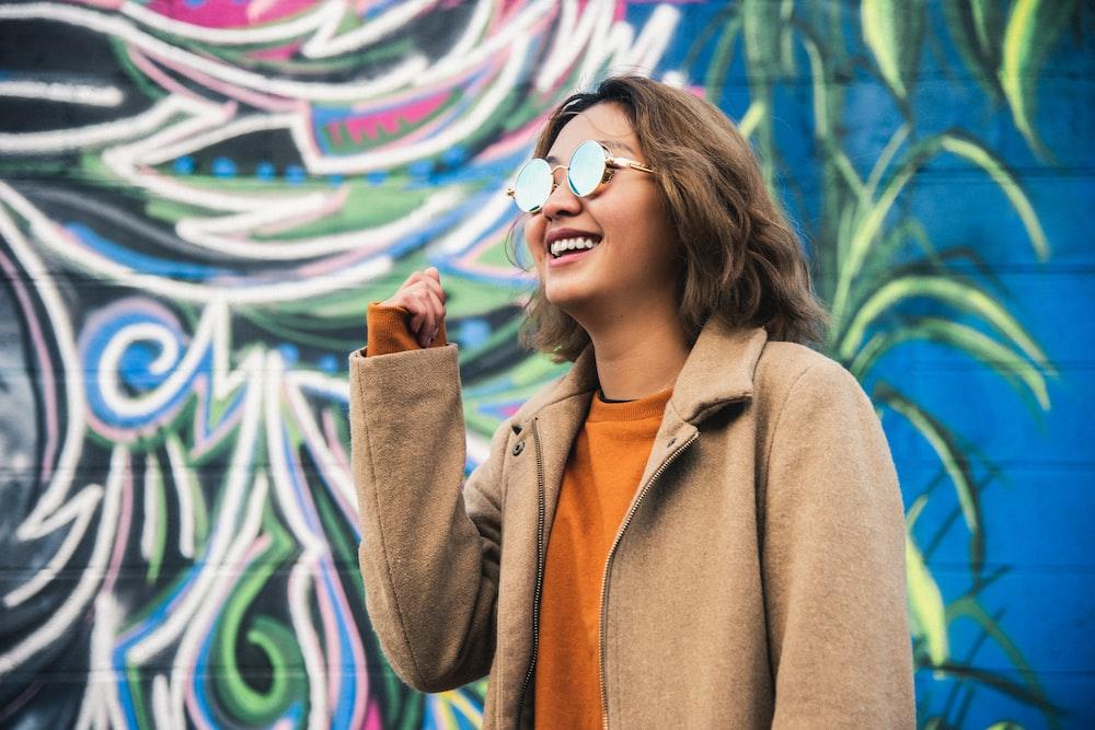 woman wearing orange shirt and beige coat wearing sunglasses while standing near graffiti wall smiling