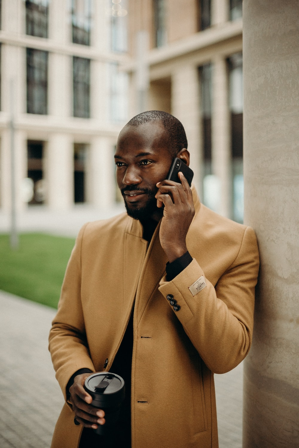 selective focus photography of man talking on phone and holding cup
