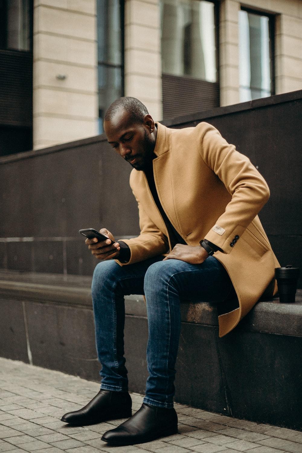 sitting man using smartphone