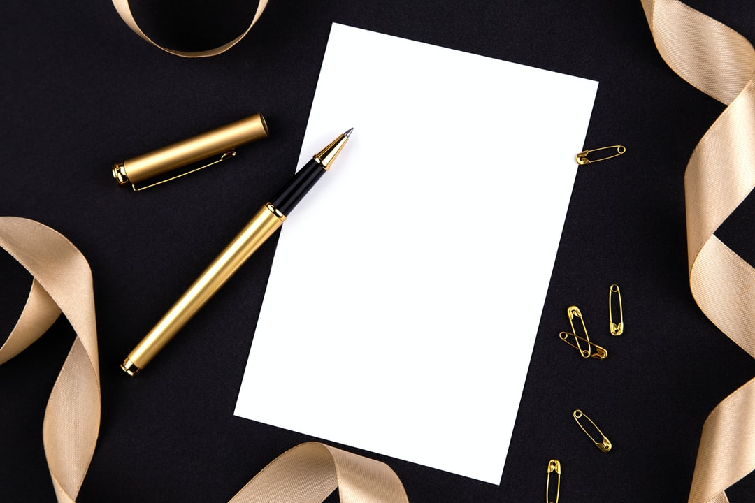Gold Pen, Ribbon, Paper Clips and Stationery On A Black Background With A White Sheet of Paper. - unsplash