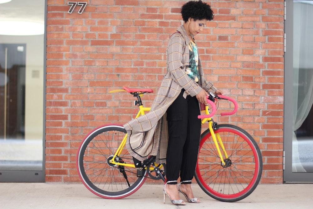 woman holding road bike near brick wall