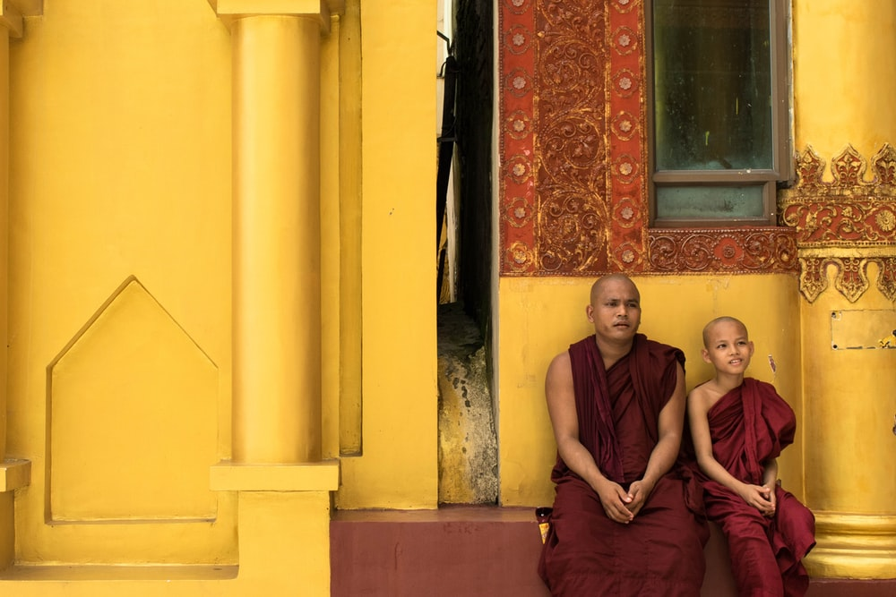 two monks sit outside yellow painted building