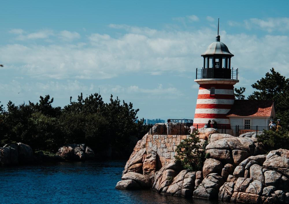 white and red striped lighthouse near body of water