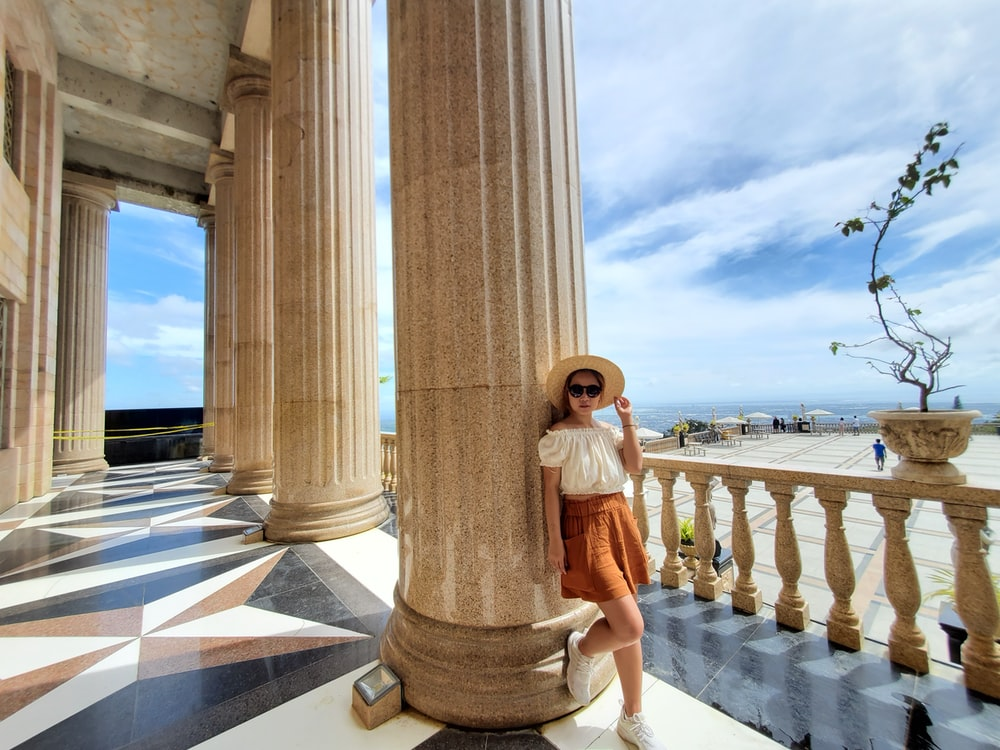 woman leaning back on pillar during day