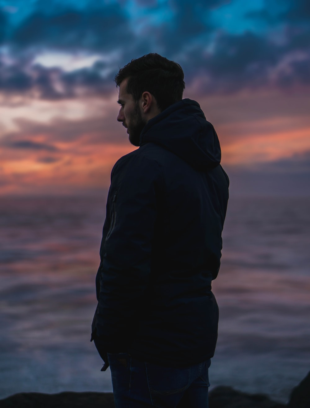 man wearing black jacket standing while facing his right side under blue and orange sky