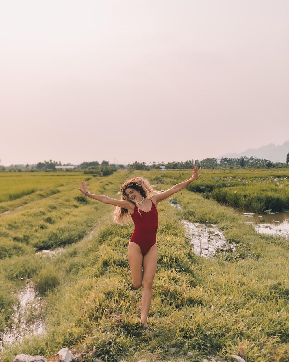 woman running in grass field wearing red swimsuit