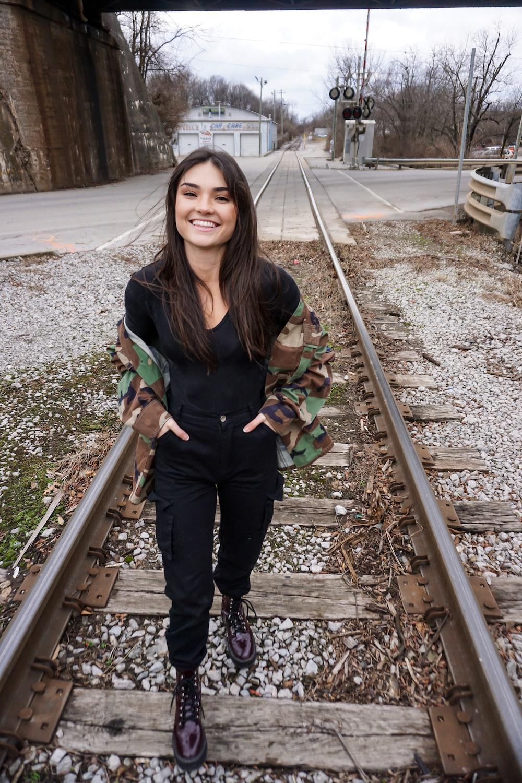 woman in black crew-neck shirt standing on train rail
