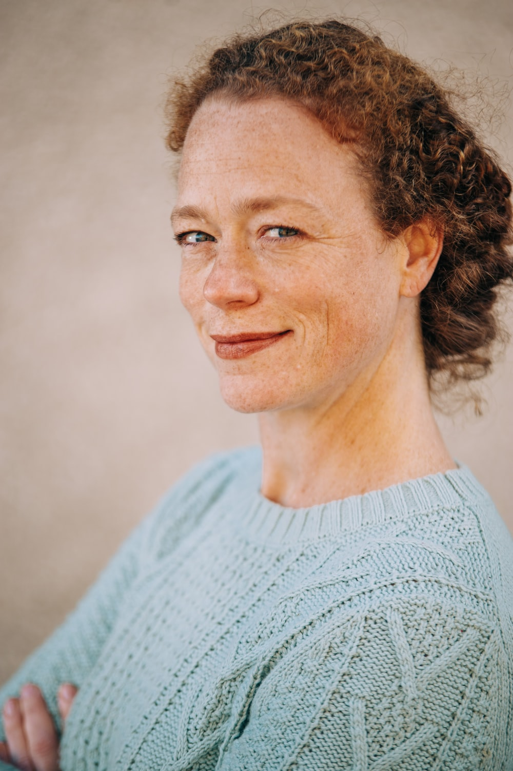 portrait photography of woman wearing teal crew-neck sweater smiling