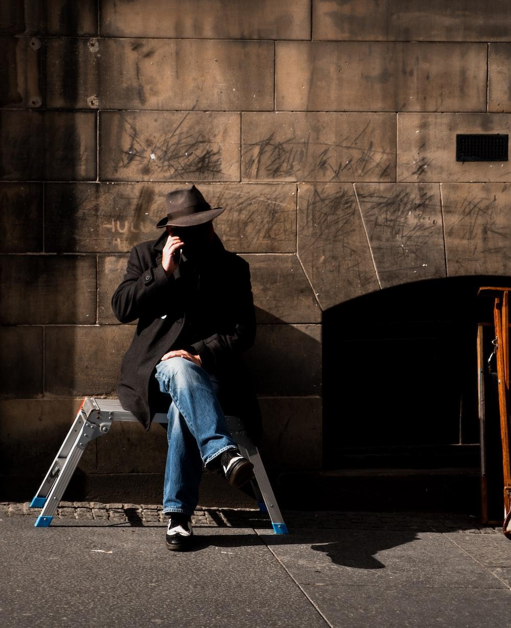 man sitting on stool near wall