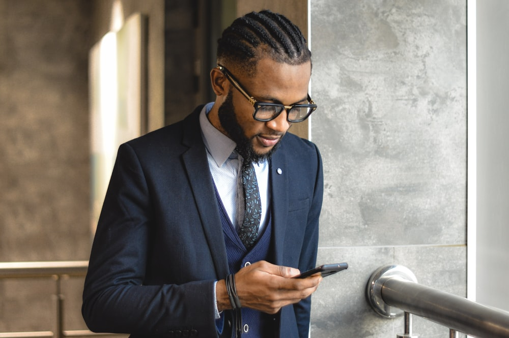 man in blue suit jacket holding smartphone