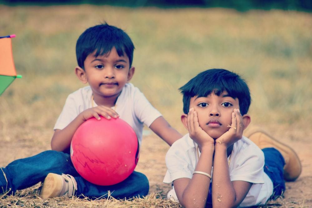 twin children wearing white crew-neck t-shirt on brown field