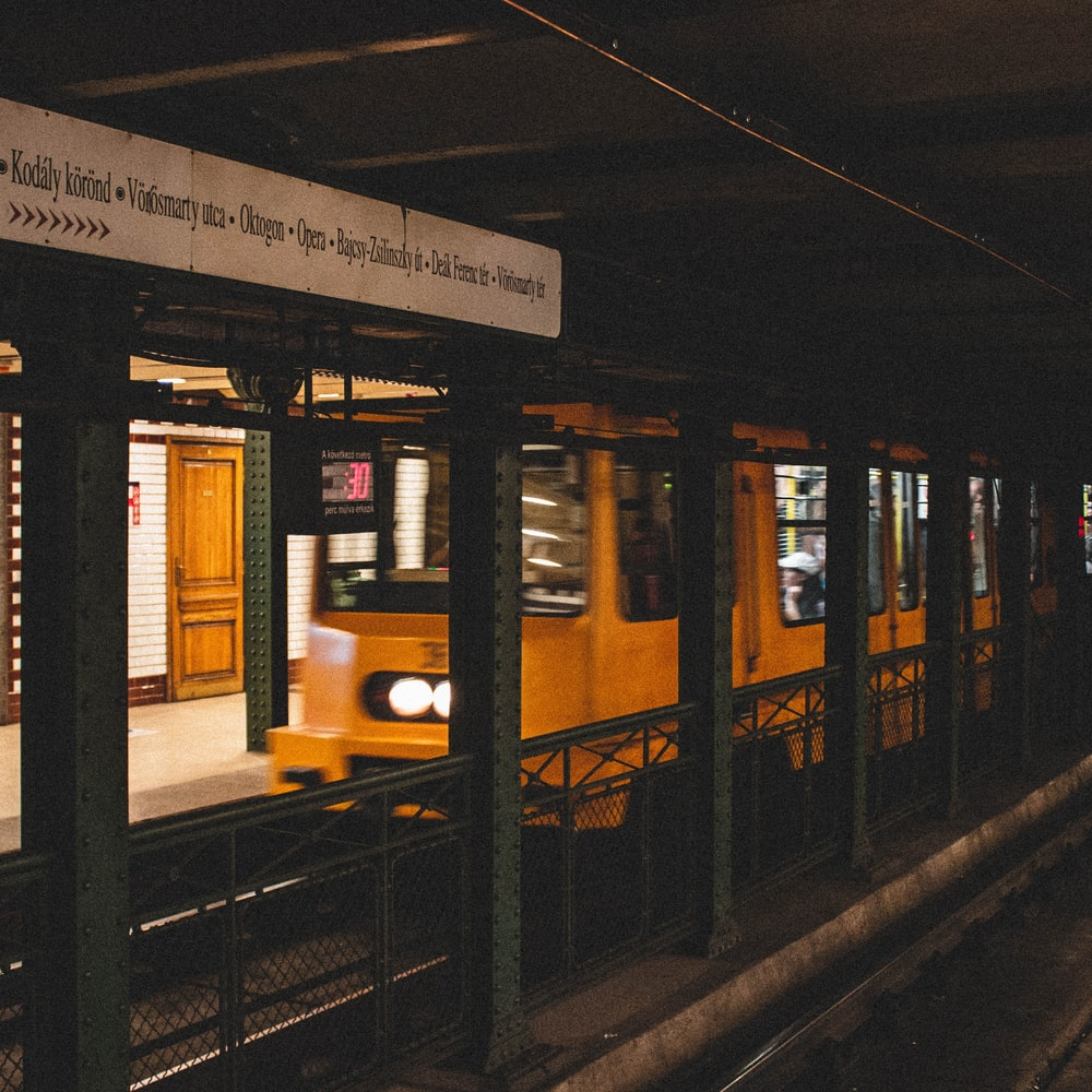 time-lapse photography of a yellow train passing in the station