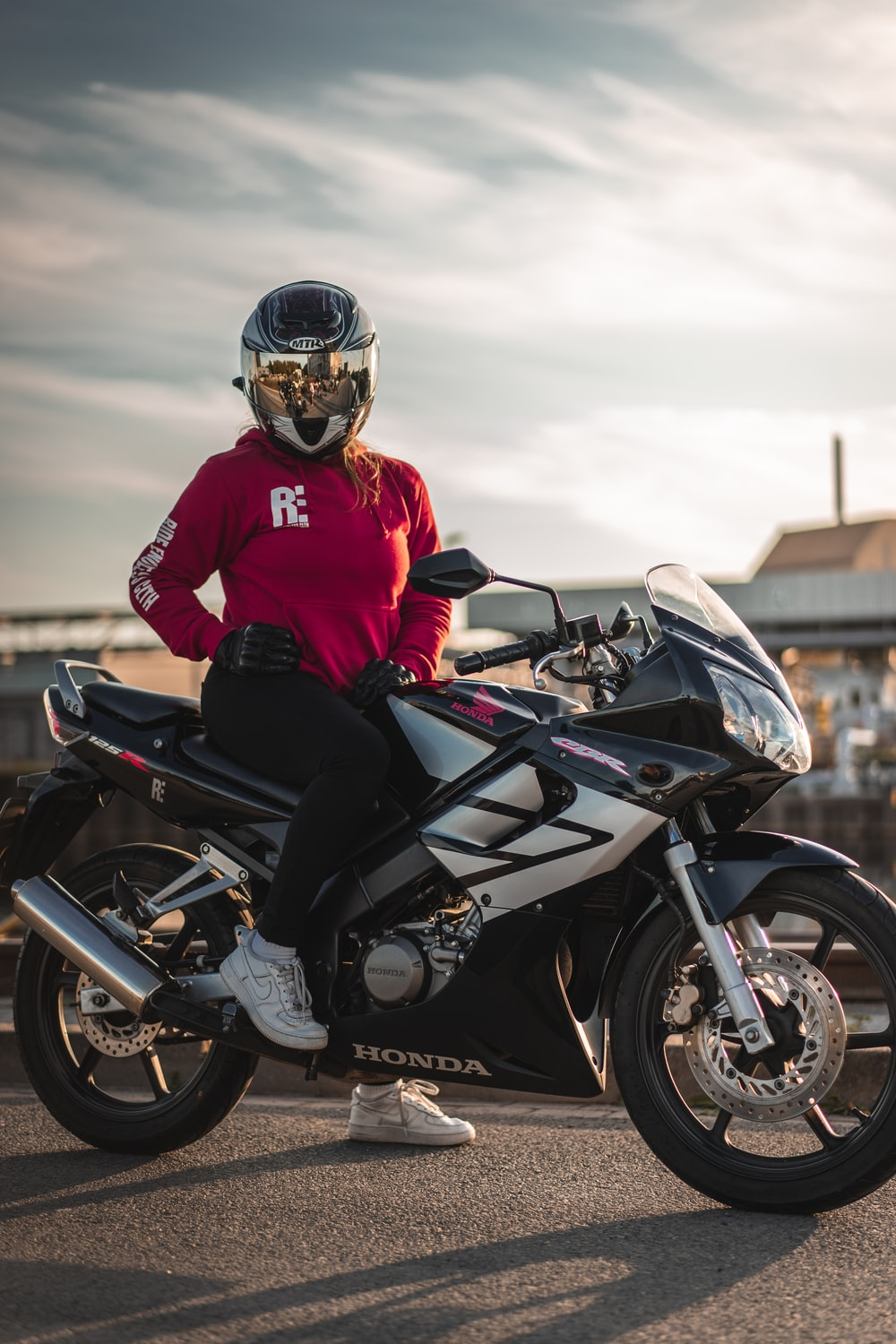 person sitting on Honda sports bike during day