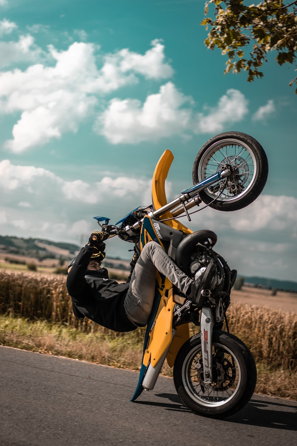 man riding yellow motocross dirt bike on road near grass during cloudy day