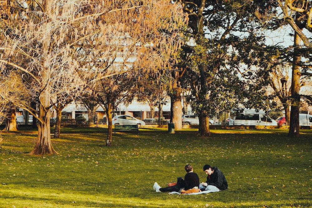 two men sitting on grass field