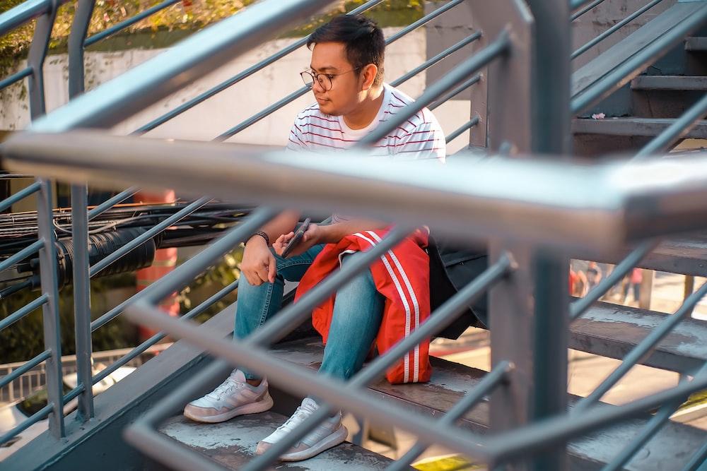 man sitting on metal stairs