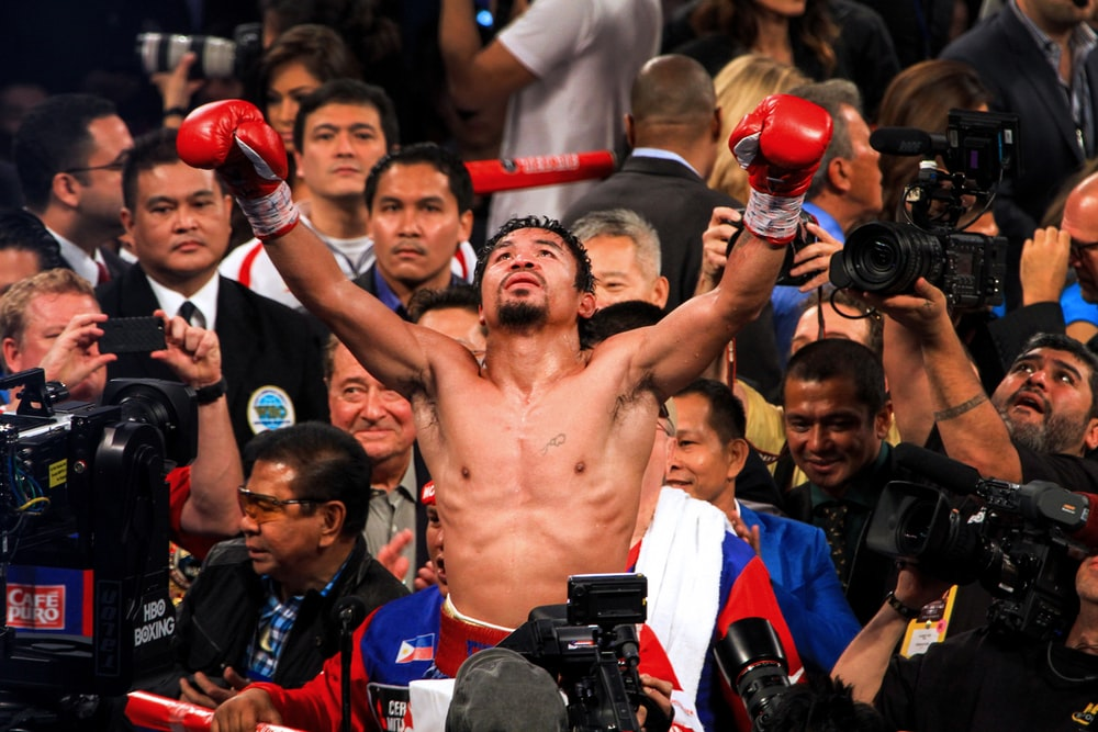Manny Pacquiao raising his hands surrounded by crowd