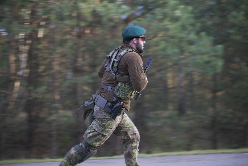 soldier man wearing sunglasses running on road