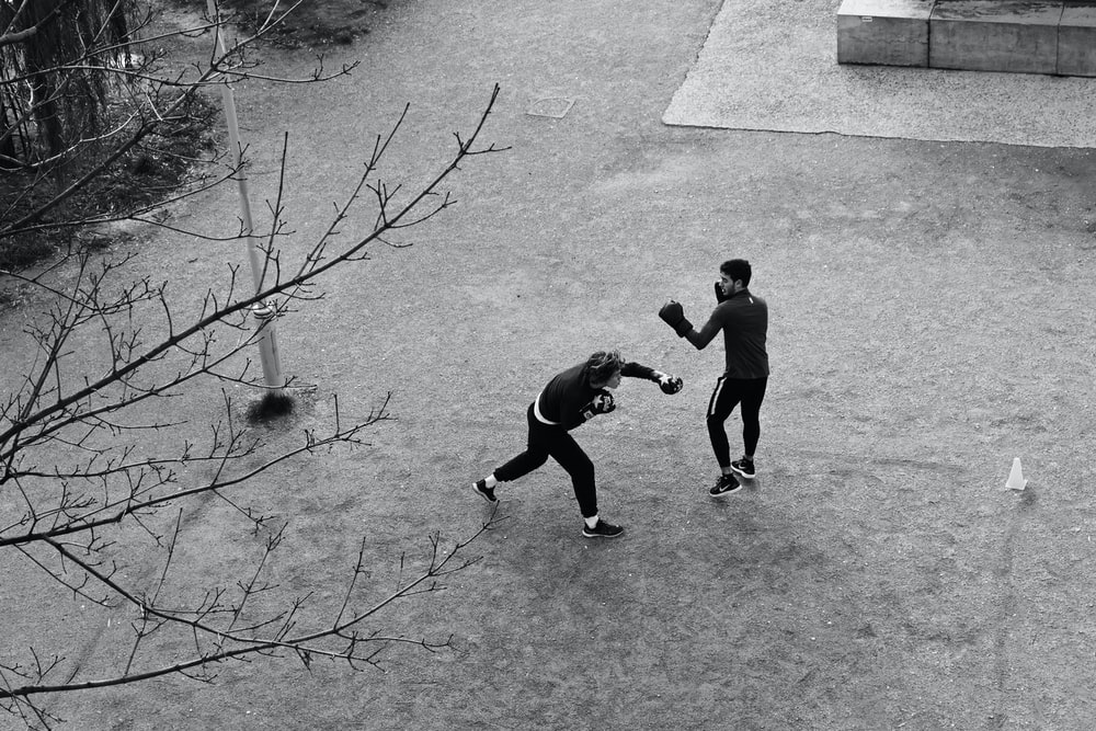 grayscale photography of two people boxing on field