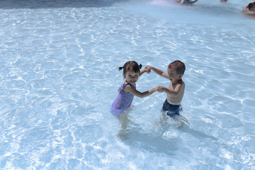 girl and boy playing in swimming pool