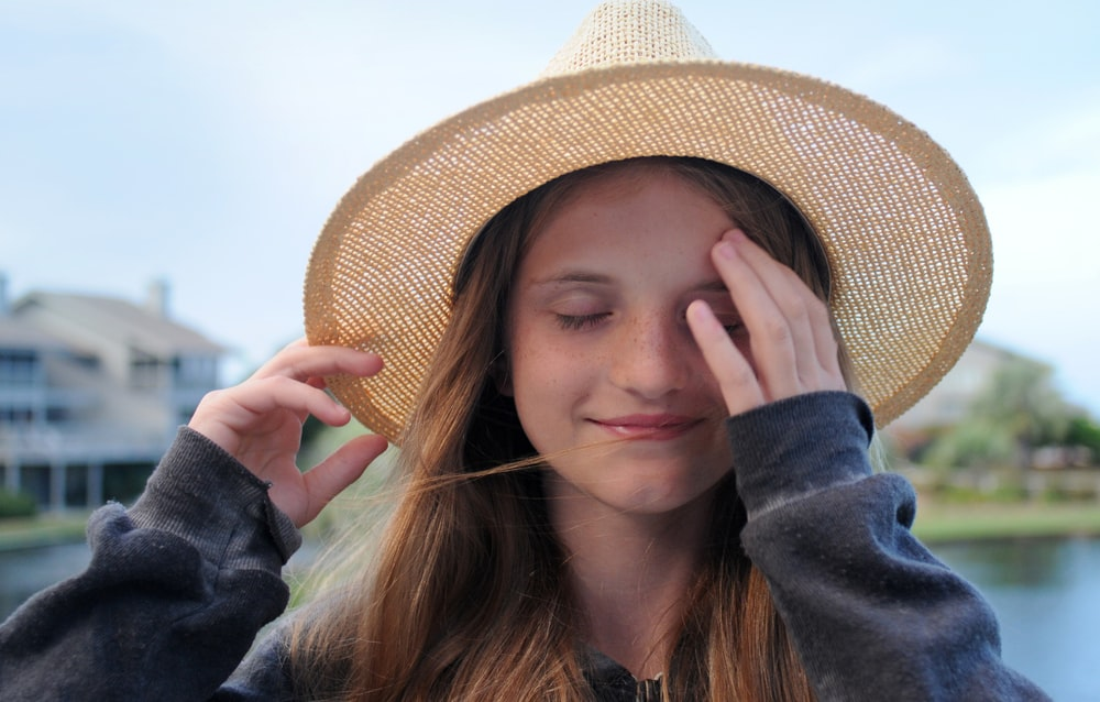 closed eyed woman wearing beige hat during day