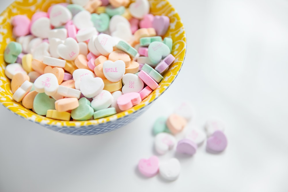 minimalist photography of bowl of variety colored heart-shaped candies