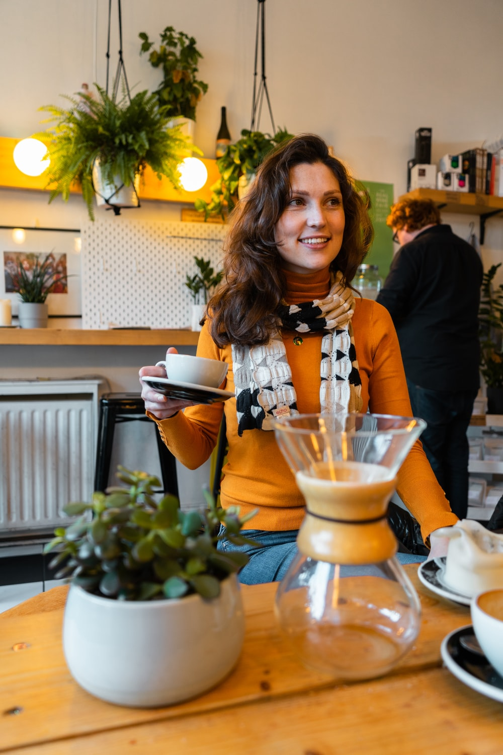 woman in orange sweater holding cup