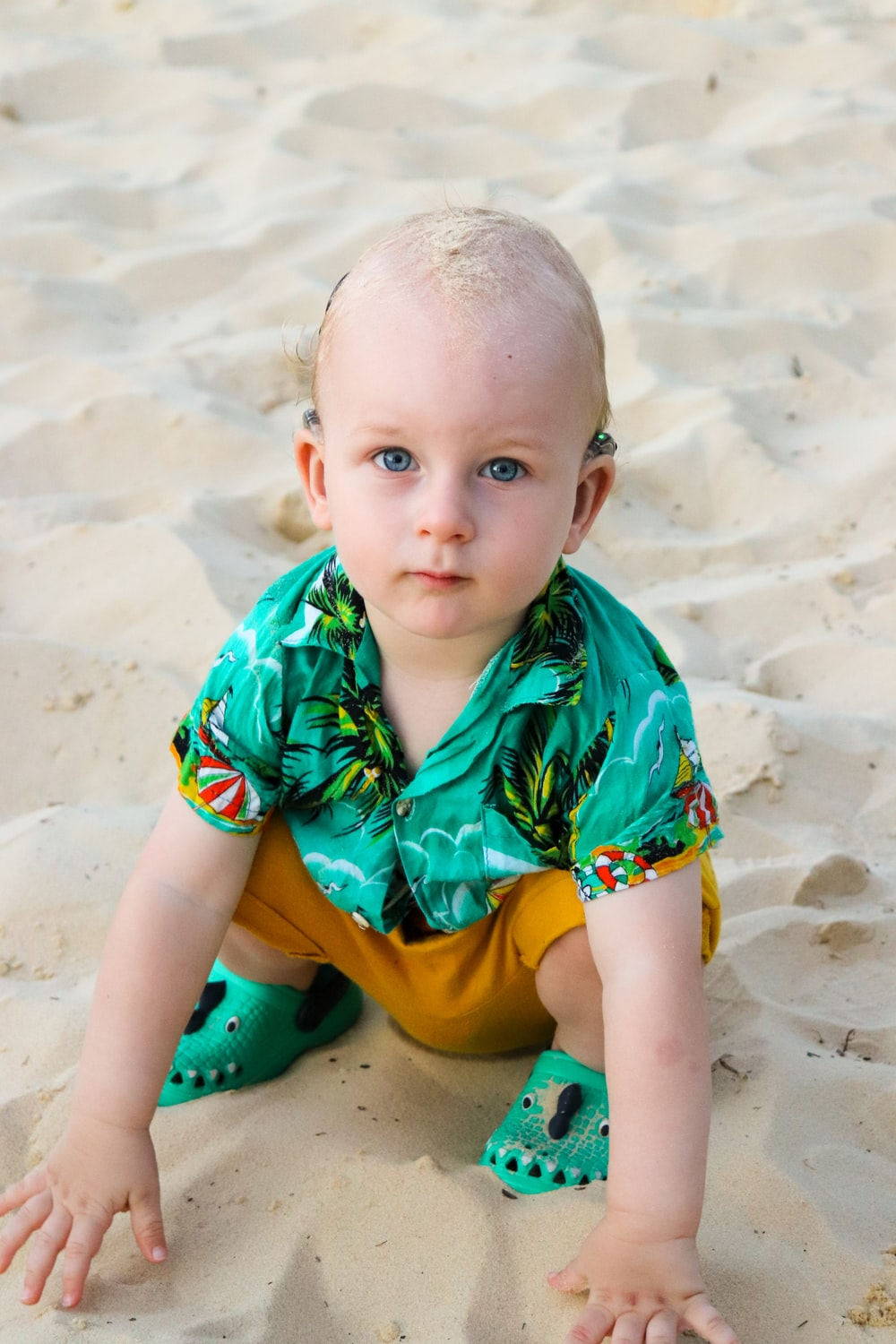 toddler in green button-up T-shirt