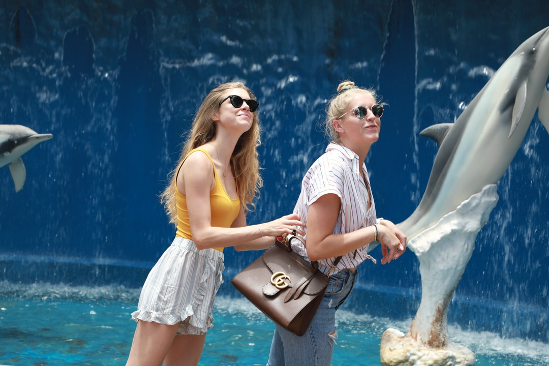 Two women having fun with dolphins at the aquarium in Hawaii.