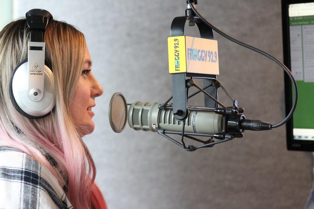 shallow focus photo of woman using white headphones