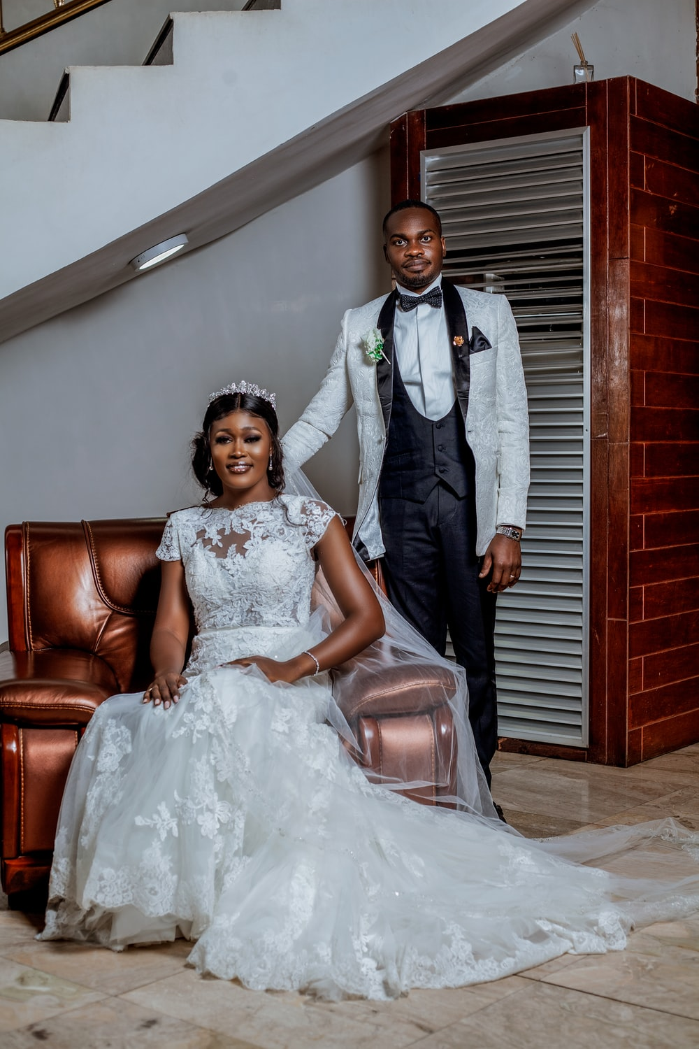groom standing beside a bride sitting on a sofa chair