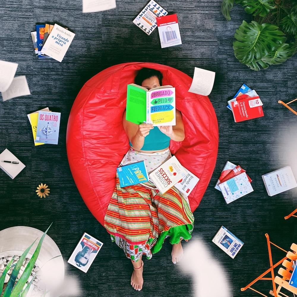 mujer, acostado, en, rojo, puf, silla, libro de lectura