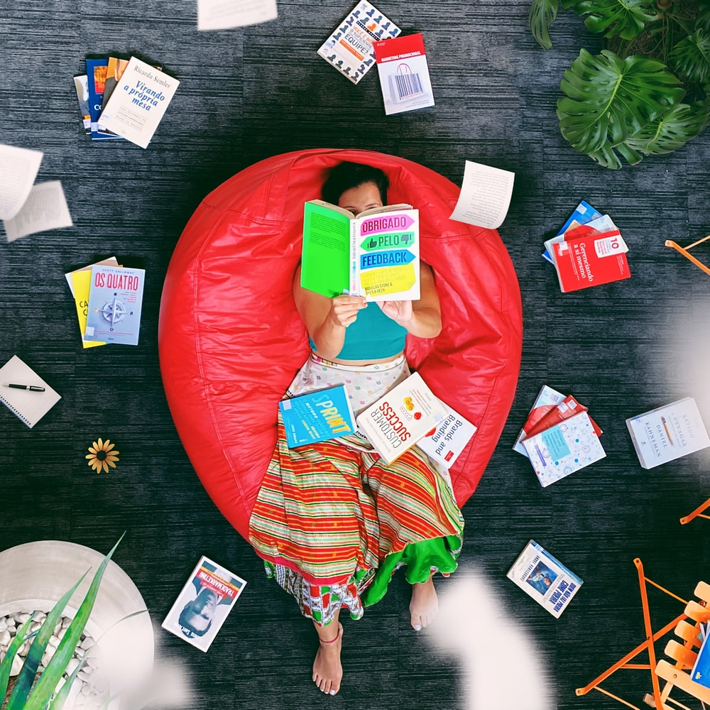 woman lying on red beanbag chair reading book