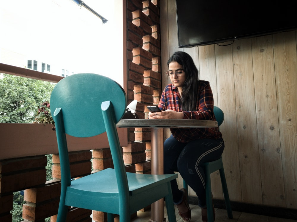 woman leaning on pedestal table