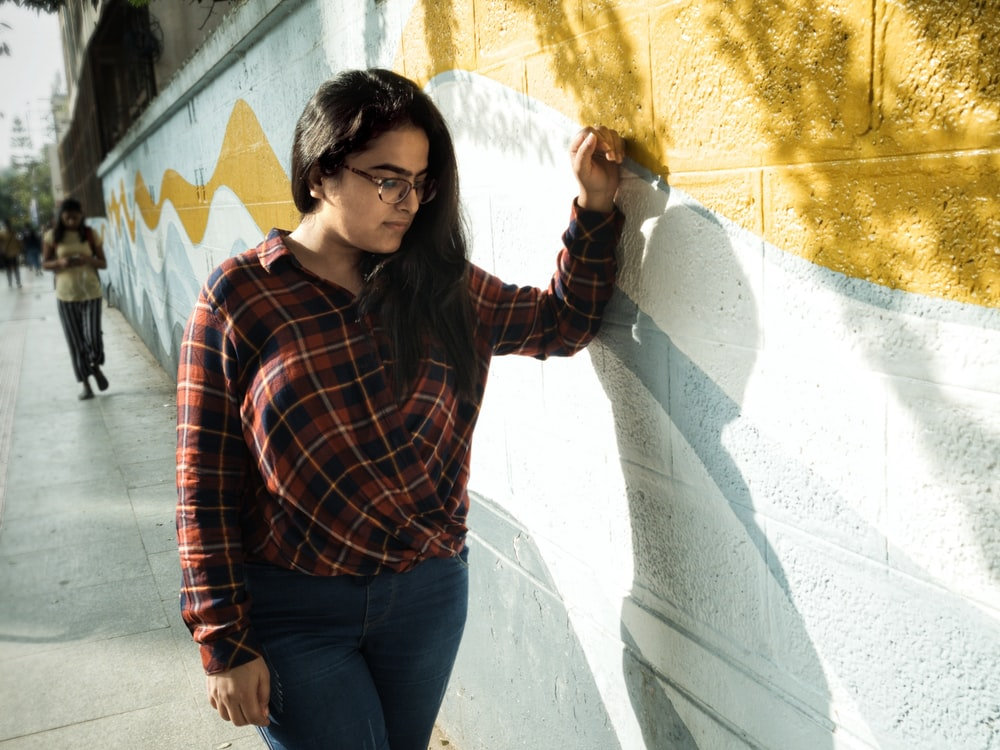 woman standing in front of brown and white painted concrete wall