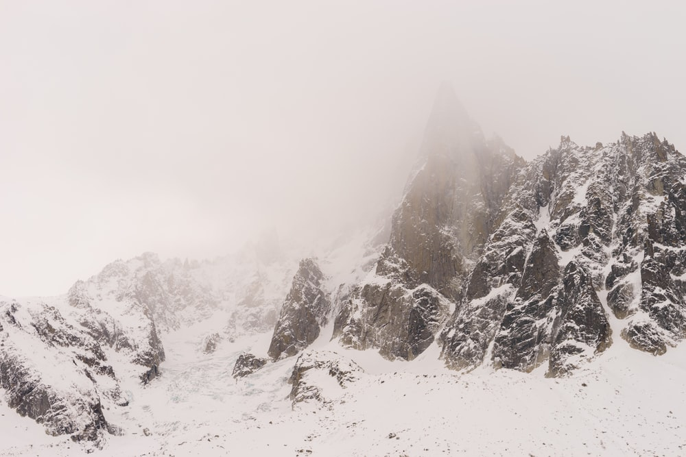 field and mountain covered with snow in foggy day