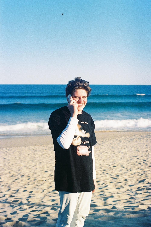 standing man talking on phone on seashore during daytime