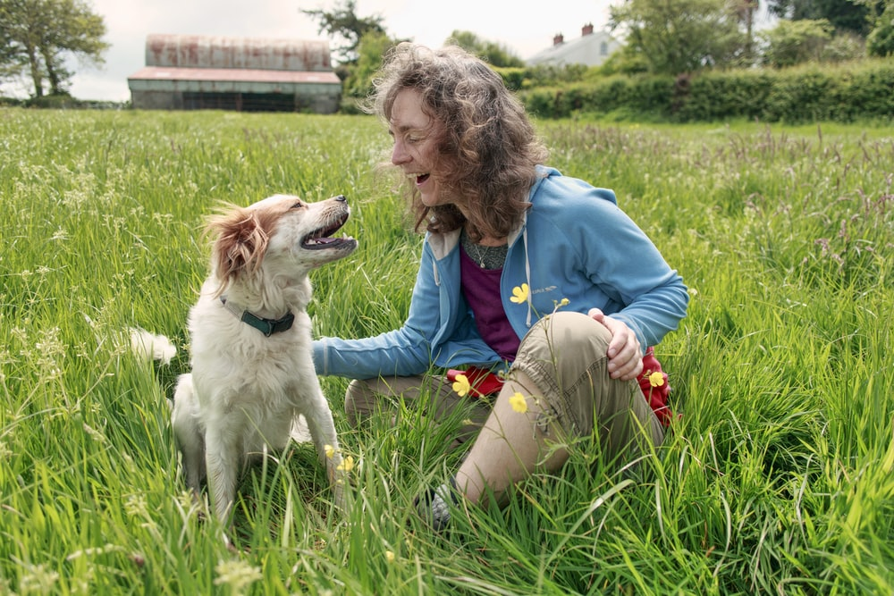 woman sitting beside sitting dog on grass during day