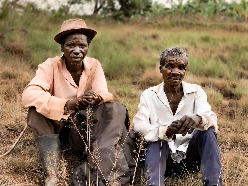 two men sitting on ground