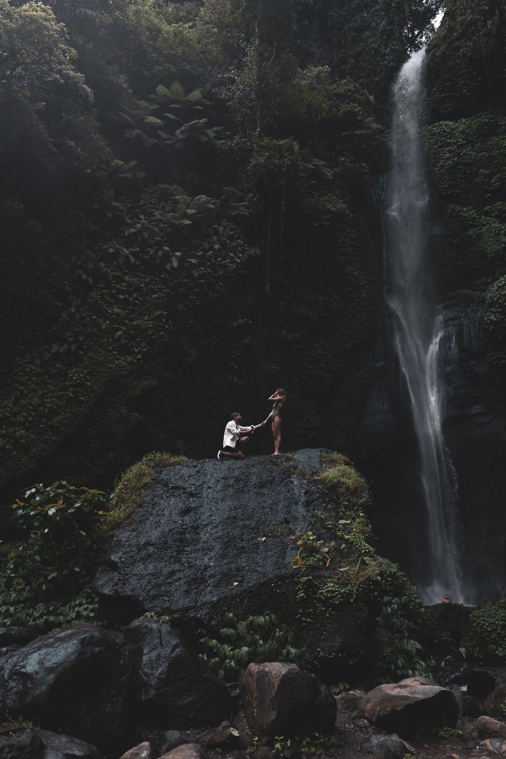man in white shirt and black shorts standing on rock near waterfalls during daytime