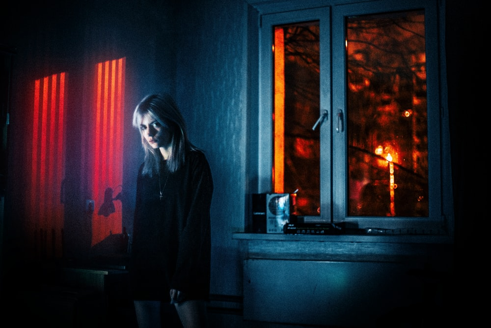 woman in black jacket standing beside window