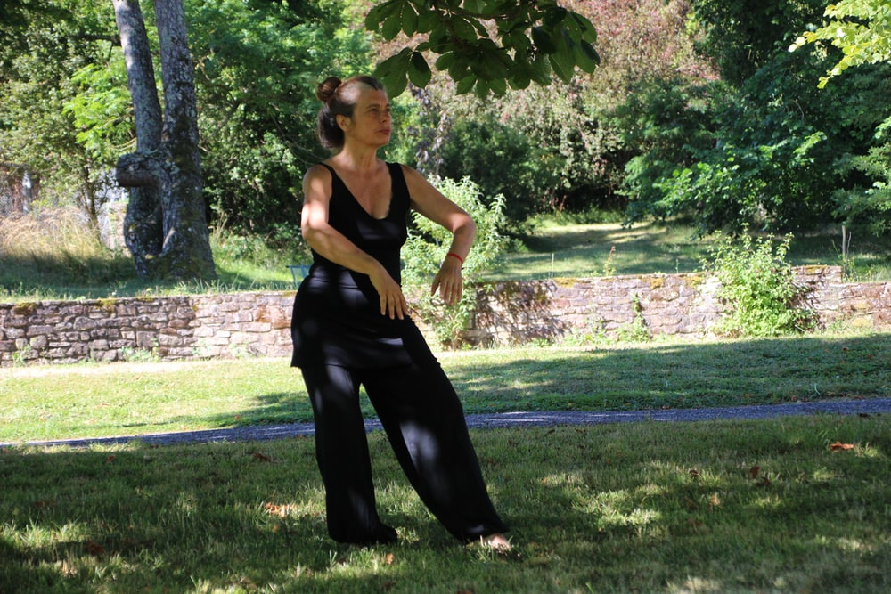 woman in black tank top and black pants standing on green grass field during daytime
